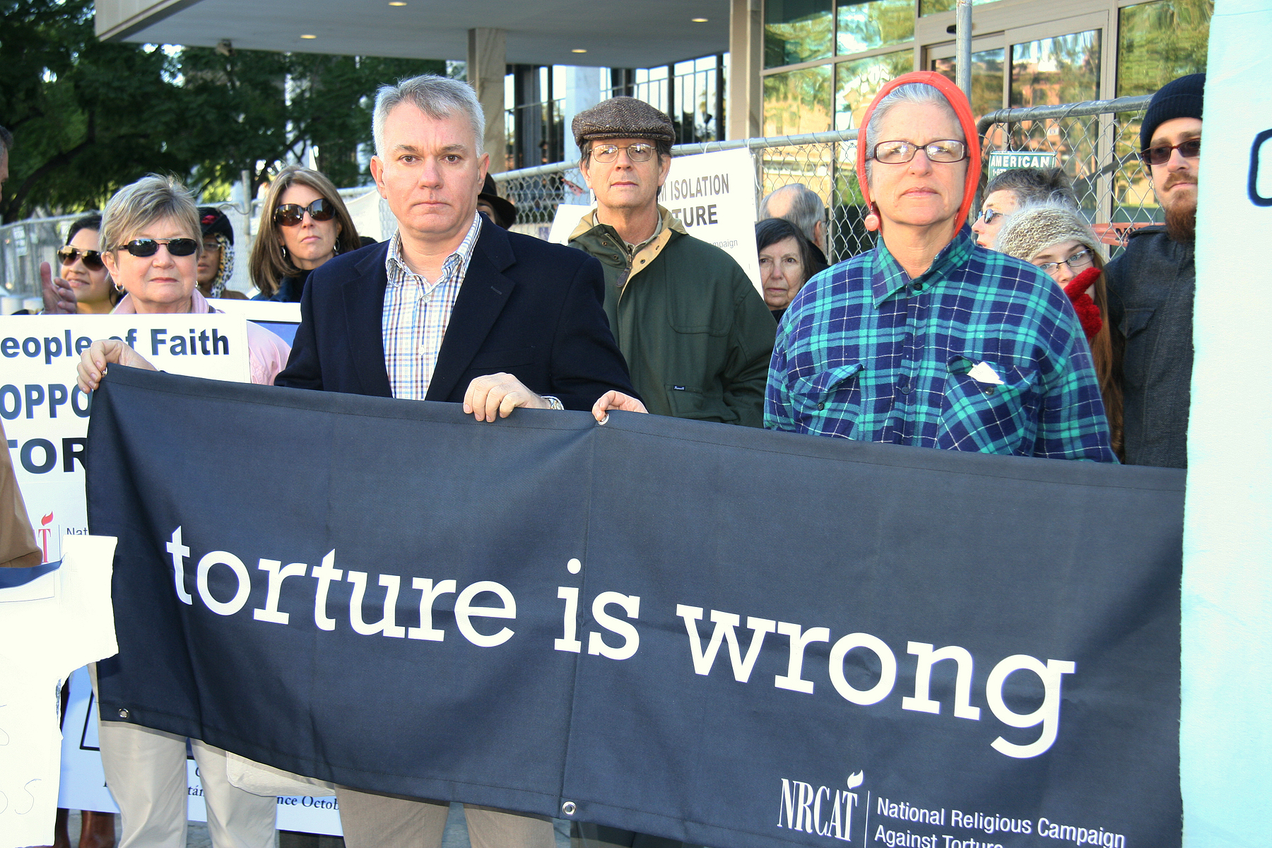 Martha holding Torture is Wrong banner 8801